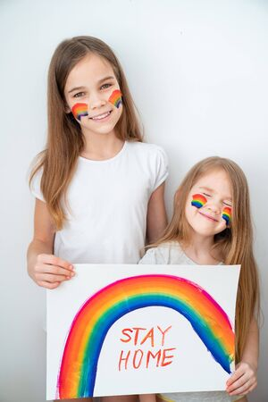 two girls with blond hair drew a rainbow and a poster stay home. flashmob chasetherainbow.