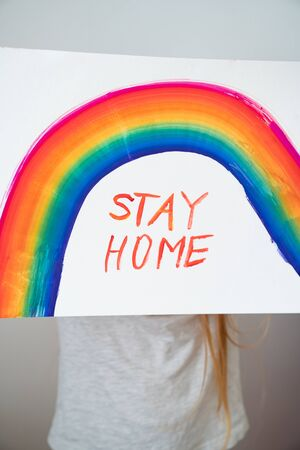 small girl with blond hair drew a rainbow and a poster stay home. flashmob chasetherainbow.