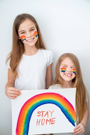 funny kid girls with blond hair drew a rainbow and a poster stay home. flashmob chasetherainbow.
