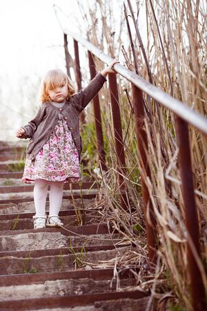 kid girl walks down the stairs with a high handrail along the dry tussocks.