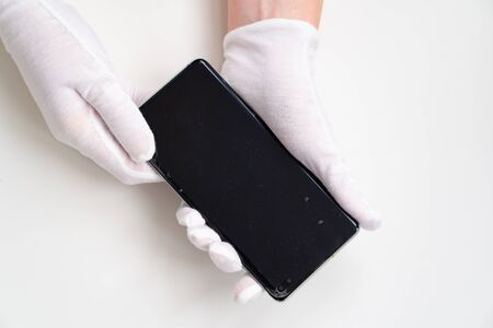 A hands is holding a mobile phone that with the old protective film. Technology concept. Фото со стока