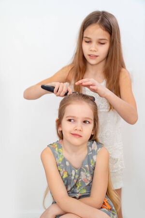 Lovely little girl brushing hair of her younger sister. older sister combing hair. care in the family.