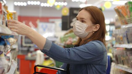 woman Buyer wearing a protective mask.Shopping during the pandemic.Emergency to buy list.Panic buying during coronavirus outbreak.Preparation for a pandemic quarantine Foto de archivo
