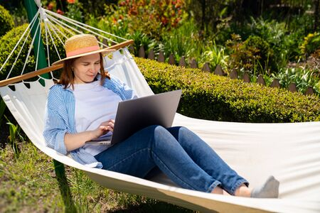 female businesswoman freelancer lies in the hammock and working on the computer. Remote working, isolation in quarantine. the social distance. Archivio Fotografico