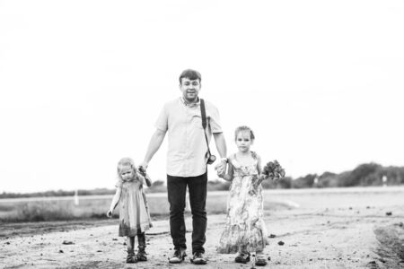 dad and little girls in a dress goes in the dirty dirt road. earth after a rain. off-road. near a field with flowers poppies. Stock Photo