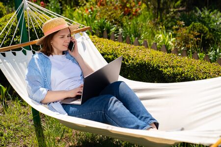 woman businesswoman freelancer lies in the hammock and working on the computer, answering phone call. Remote working, isolation in quarantine. the social distance.