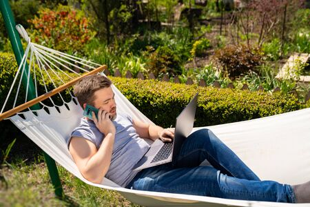 man businessman freelancer lies in the hammock and working on the computer, answering a phone call. Remote working, isolation in quarantine. the social distance.