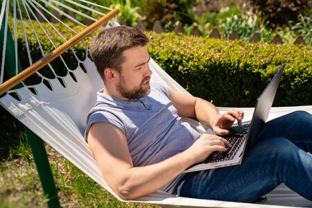 male businessman freelancer lies in the hammock and working on the computer. Remote working, isolation in quarantine. the social distance.