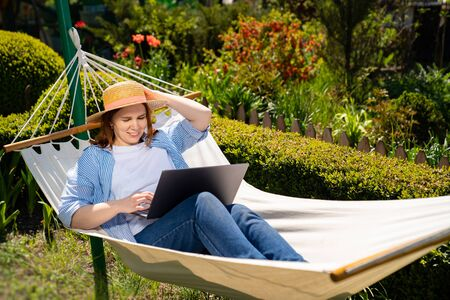 businesswoman female freelancer lies in the hammock and working on the computer. Remote working, isolation in quarantine. the social distance.