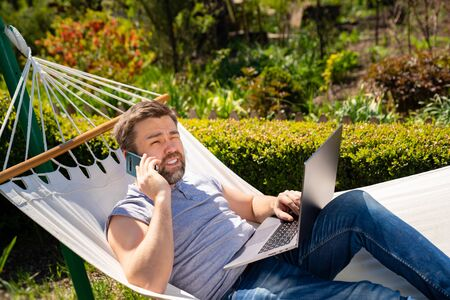 male businessman freelancer lies in the hammock and working on the computer, answering a phone call. the social distance. Remote working, isolation in quarantine. Archivio Fotografico