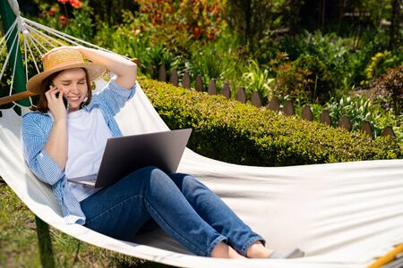 woman businesswoman freelancer in hat lies in the hammock and working on the computer, answering phone call. Remote working, isolation in quarantine. the social distance.