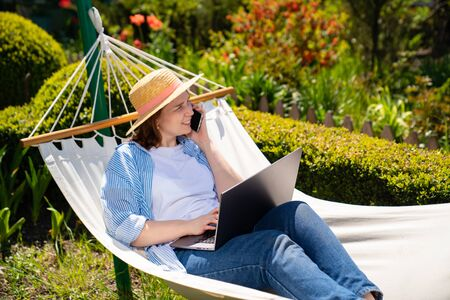 female businesswoman freelancer lies in the hammock and working on the computer, answering phone call. Remote working, isolation in quarantine. the social distance. Archivio Fotografico