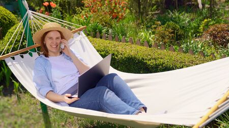 businesswoman freelancer in hat lies in the hammock and working on the computer, answering phone call. Remote working, isolation in quarantine. the social distance.