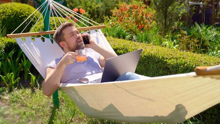 male businessman freelancer lies in hammock and working on computer, answering phone call, drinking juice. Remote working, isolation in quarantine. social distance.