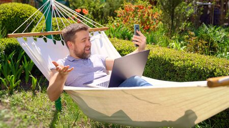 male businessman freelancer lies in the hammock and working on the computer, answering a live video phone call. Remote working, isolation in quarantine. the social distance.
