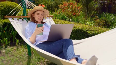 female businesswoman freelancer lies in the hammock and working on the computer, answering a live video phone call, makes a selfie photo. Remote working, isolation in quarantine. the social distance. Archivio Fotografico