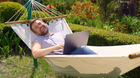 man businessman freelancer lies in the hammock and working on the computer. Remote working, isolation in quarantine. the social distance.