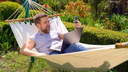 freelancer businessman lies in the hammock and working on the computer, answering a live video phone call. Remote working, isolation in quarantine. the social distance.