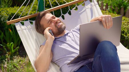 male businessman freelancer lies in the hammock and working on the computer, answering a phone call. Remote working, isolation in quarantine. the social distance.