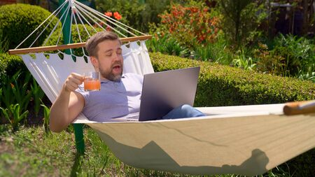 male businessman freelancer lies in hammock and working on computer, drinking juice. Remote working, isolation in quarantine. social distance.