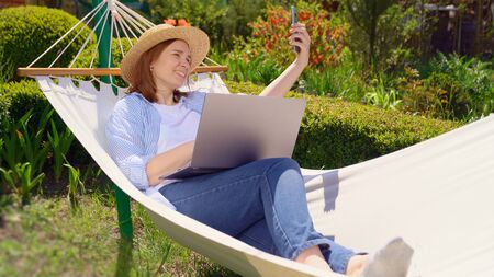 female businesswoman freelancer lies in the hammock and working on the computer, answering a live video phone call, makes a selfie photo. Remote working, isolation in quarantine. the social distance.