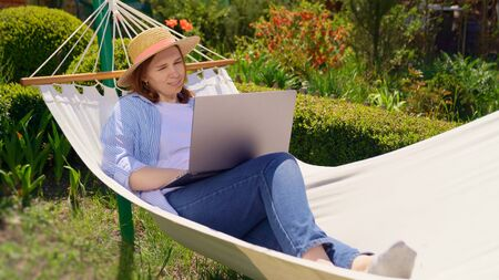 female businesswoman freelancer lies in the hammock and working on the computer. Remote working, isolation in quarantine. the social distance.