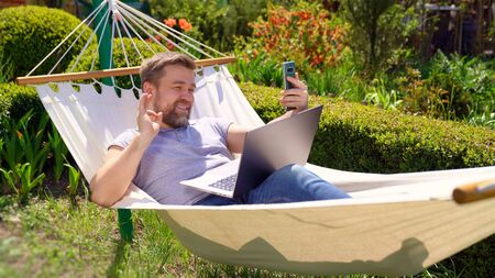 businessman freelancer lies in the hammock and working on the computer, answering a live video phone call. Remote working, isolation in quarantine. the social distance.