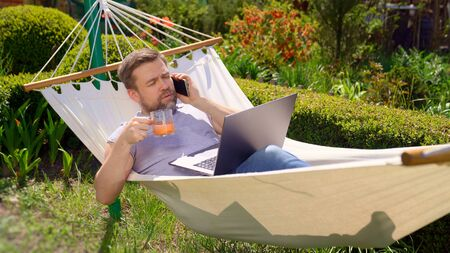 male businessman freelancer lies in hammock and working on computer, answering phone call, drinking juice. Remote working, isolation in quarantine. social distance. Archivio Fotografico