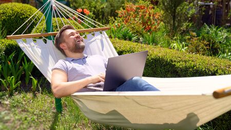 happy man businessman freelancer lies in the hammock and working on the computer. Remote working, isolation in quarantine. the social distance.