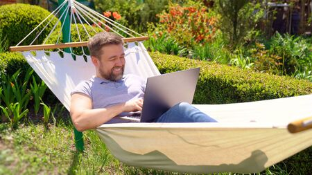 male businessman freelancer lies in the hammock and working on the computer. Remote working, isolation in quarantine. the social distance. Archivio Fotografico