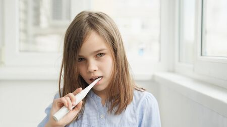 teen girl in the morning cleans the teeth electric toothbrush. The concept of daily care and hygiene of the oral cavity. prevention of dental caries. Archivio Fotografico