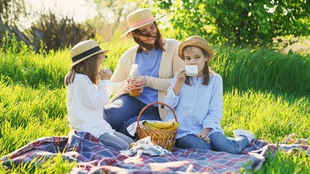 Mother with her daughters in hats at a picnic on the lawn and pour the juice. holidays and trips with family out of town on nature. windy spring weather.
