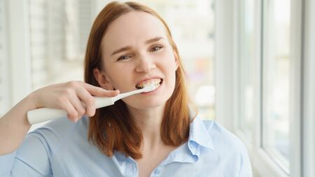 woman in the morning cleans the teeth electric toothbrush. The concept of daily care and hygiene of the oral cavity. prevention of dental caries.