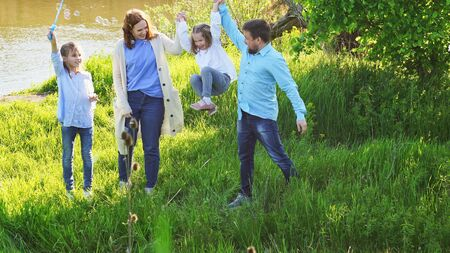 Cheerful happy family having a picnic and playing inflate soap bubbles. vacations and trips out of town on nature.