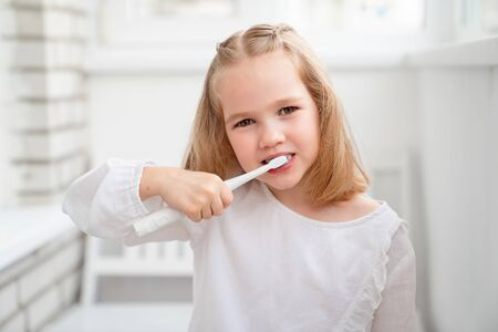 funny kid girl in the morning cleans the teeth electric toothbrush. The concept of daily care and hygiene of the oral cavity. prevention of dental caries. Archivio Fotografico