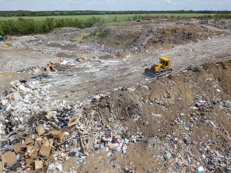 yellow tractor on dump in a field. garbage collection, environmental disaster. pollution of the environment. trucks carrying waste. Фото со стока