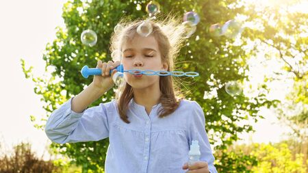 little girl inflate soap bubbles on a picnic in a field in the spring. the concept of travel and outdoor leisure.