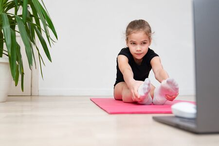 girl teen sports home. gymnastics online. dancing on the quarantine. stretching on a gym Mat.