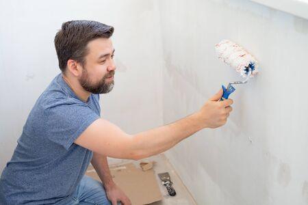 Mann Malerei Rollenwand mit weißer Farbe. Bau- und Reparaturarbeiten zu Hause. Standard-Bild