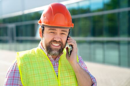 A man building inspector in a construction helmet just got a phone call safety during construction work. the decision of business matters on the site.