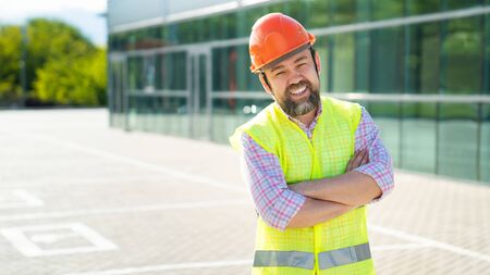 male foreman or building inspector in the vest and protective helmet standing on the background of the new structure. the concept of professional activity.