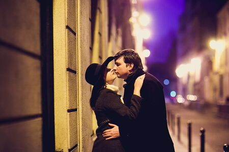 girl in hat and a man kiss and walking through the night streets of Paris. romantic city for travel. 免版税图像