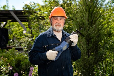 A elderly man with a beard in a hardhat and glasses with a reciprocating saber saw. construction work. compliance with safety regulations. employment in retirement.