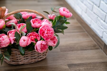 bouquet of pink peonies in a basket on the floor. gift and interior decoration with fresh flowers.
