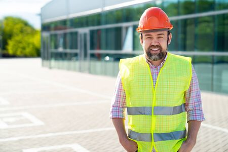 male foreman or building inspector in the vest and protective helmet standing on the background of the new structure. the concept of professional activity. Banco de Imagens