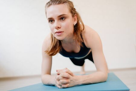 the girl is engaged in sports at home online workouts on the laptop. fitness exercise plank