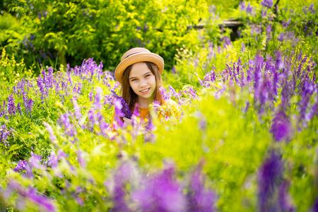 teen girl in hat picking a bouquet of purple wildflowers in a meadow. the beauty of nature. walks in outdoor air