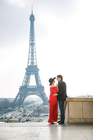 a man and a woman in red dress and in a hat on the Eiffel tower in Paris. the symbol of France. a romantic journey through Europe.