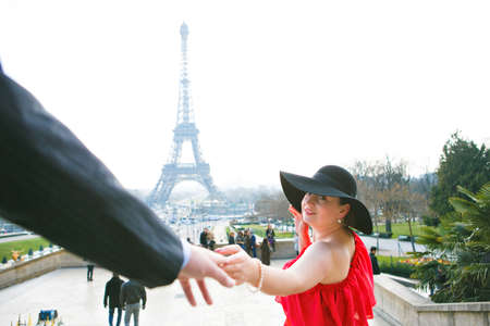 man and woman in red dress walking in Paris on the Eiffel tower. a romantic trip in the spring in France. Zdjęcie Seryjne