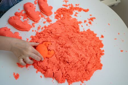 hands little girl playing with kinetic sand. the development of fine motor skills. educational games. Banque d'images
